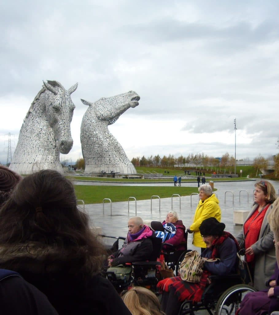 Art group taking in the views of The Kelpies on a cloudy by happy day.